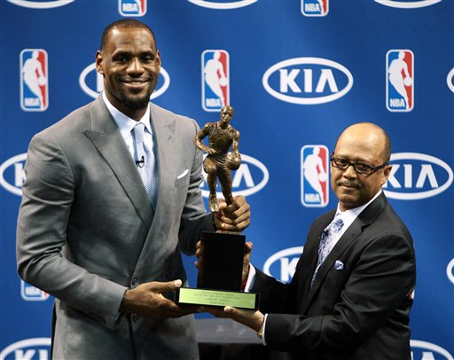 """Miami Heat's LeBron James, left, poses with the NBA MVP trophy alongside Kia's Percy Vaughn, Saturday, May 12, 2012, in Miami. Calling the honor """"overwhelming"""" but pointing to a """"bigger goal,"""" James on Saturday became the eighth player in NBA history to win the MVP award three times. (AP Photo/El Nuevo Herald, Roberto Koltun) MAGS OUT Heat13;HWW13 Heat News rk"""