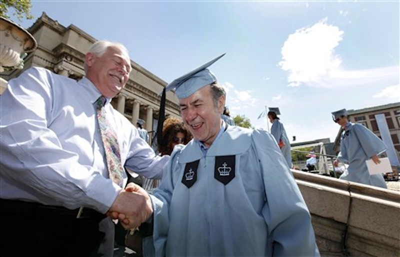 Columbia University janitor Gac Filipaj, center, is congratulated by his boss, Donald Schlosser, the assistant vice president of facility operations, during the Columbia University School of General Studies graduation, Sunday, May 13, 2012, in New York. Filipaj, an ethnic Albanian who left his native Montenegro 20 years ago to escape war, is graduating with honors after 12 years of balancing studies and his full-time job. (AP Photo/Jason DeCrow)