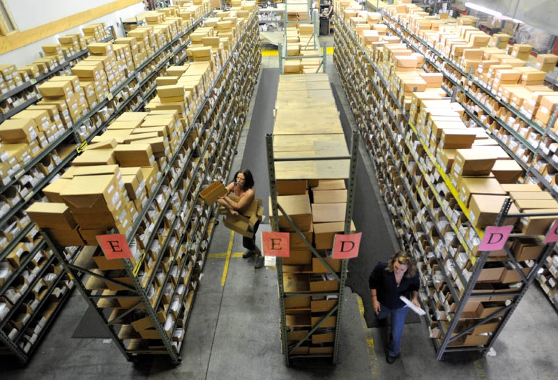 Workers at Johnny's Selected Seeds sort packages at the shipping center in Winslow.