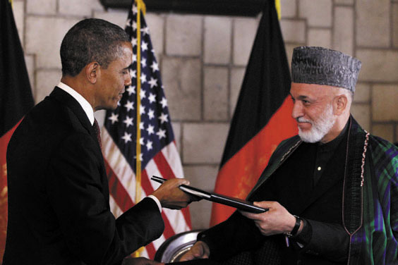 DEAL: President Barack Obama and Afghan President Hamid Karzai sign an agreement Wednesday, setting postwar promises and expectations, at the presidential palace in Kabul.