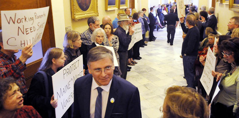 DOING BETTER: Protesters chant Tuesday as Democrat Senator Chris Johnson, of Somerville, walks to a morning session at the Statehouse. A variety of groups, united as Maine Can Do Better, chanted between the House and Senate in opposition to a proposed budget.