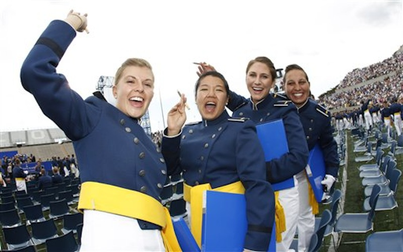 """From left, cadets Anna Gault of Aurora, Ill., Linda Laui of Honolulu, Hi., Jamie Levesque of Orange County, Cal., and Kira A. Gonzalez of Kansas City, Ks., smoke cigars after the graduation ceremony at the United States Air Force Academy in Air Force Academy, Colo., on Wednesday, May 23, 2012. President Barack Obama declared Wednesday the world has a """"new feeling about America"""" and more respect for its leadership, weaving re-election themes into a commencement speech to jubilant graduates of the U.S. Air Force Academy. (AP Photo/David Zalubowski)"""