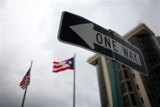 In this May 4, 2012 photo, the flags of Puerto Rico and the U.S. wave behind an English one-way traffic sign in Guaynabo, Puerto Rico, one of only a few places in Puerto Rico with street signs in English. Puerto Rico's Governor Luis Fortuno is trying to do what more than a century of American citizenship has failed to accomplish: teach Puerto Ricans to speak English as well as they do Spanish. (AP Photo/Ricardo Arduengo)