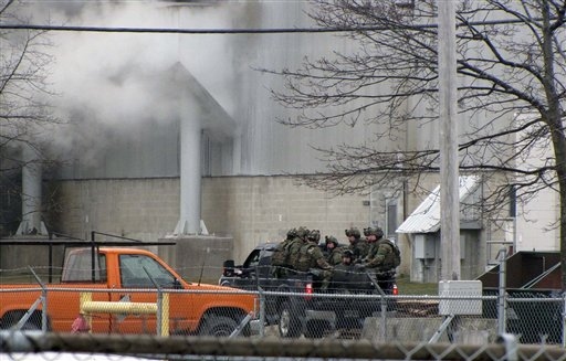 A team of Maine State Police tactical officers are taken by pickup truck into the Verso paper mill on March 14, 2012 in Jay during a standoff with a suspect Francis Smith III.