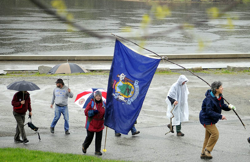 Marchers head out of the bulkhead Tuesday on the Kennebec River in Hallowell to Augusta raise awareness about environmental and economic issues.