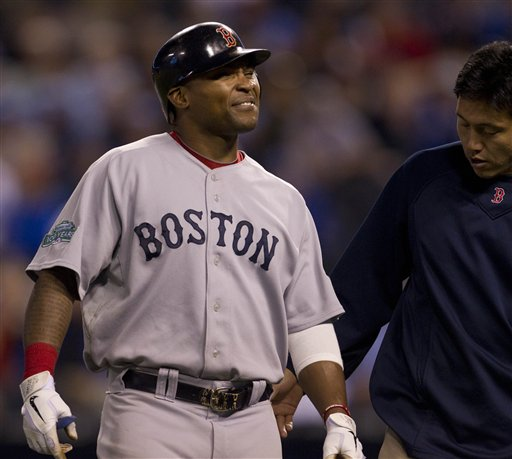 Boston Red Sox's Marlon Byrd, left, is checked by a trainer after trying to bunt during the ninth inning a baseball game against the Kansas City Royals in Kansas City, Mo., Wednesday, May 9, 2012. The Royals defeated the Red Sox 4-3. (AP Photo/Orlin Wagner)