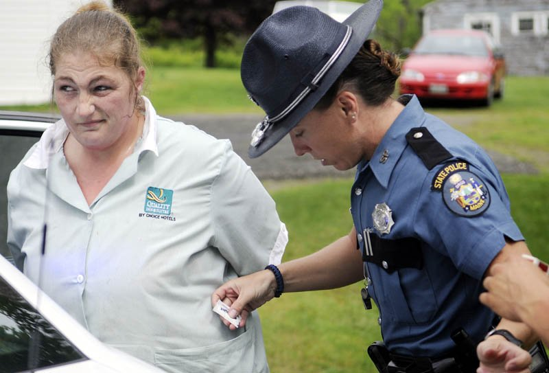 State Trooper Diane Perkins-Vance removes items from Angie Soucy's pockets moments after Soucy was arrested for allegedly dragging Kennebec County Deputy Nathan McNally with her car Tuesday in Belgrade. McNally stopped Soucy's vehicle and attempted to arrest her when she drove off with his hand stuck in her vehicle, according to police. McNally was not injured.