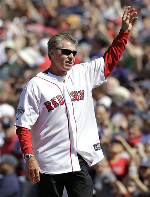 Former Boston Red Sox first baseman Bill Buckner waves to cheering fans at Fenway Park in Boston on April 20, 2012, during a celebration of the 100th anniversary of the first regular-season game at Fenway Park.