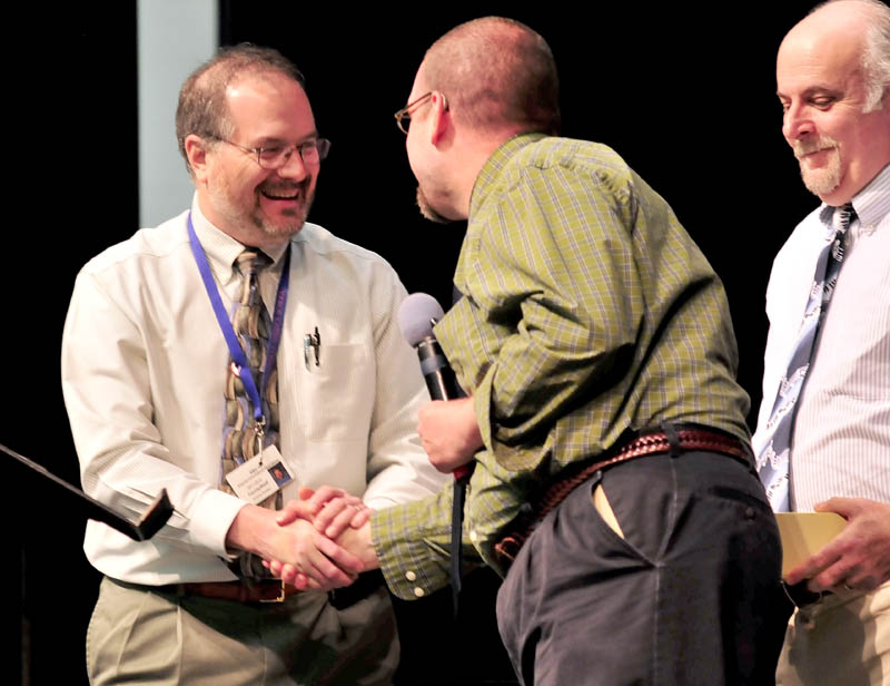 WELL DONE: Messalonskee High School music teacher Andy Forster, left, is congratulated by Mount Blue teacher Steve Muise after it was announced during a school assembly on Tuesday that Forster was named Maine Music Teacher of the Year. At right is Messalonskee teacher Kevin Rhein.