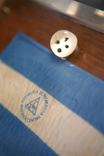 A container of moon rocks and a small Nicaraguan flag are shown at the office of lawyer Richard Wright Friday, May 18, 2012, in Las Vegas. The plaque and moon rocks were originally presented as a gift to the people of Nicaragua by President Nixon. (AP Photo/Las Vegas Review-Journal, Ronda Churchill)