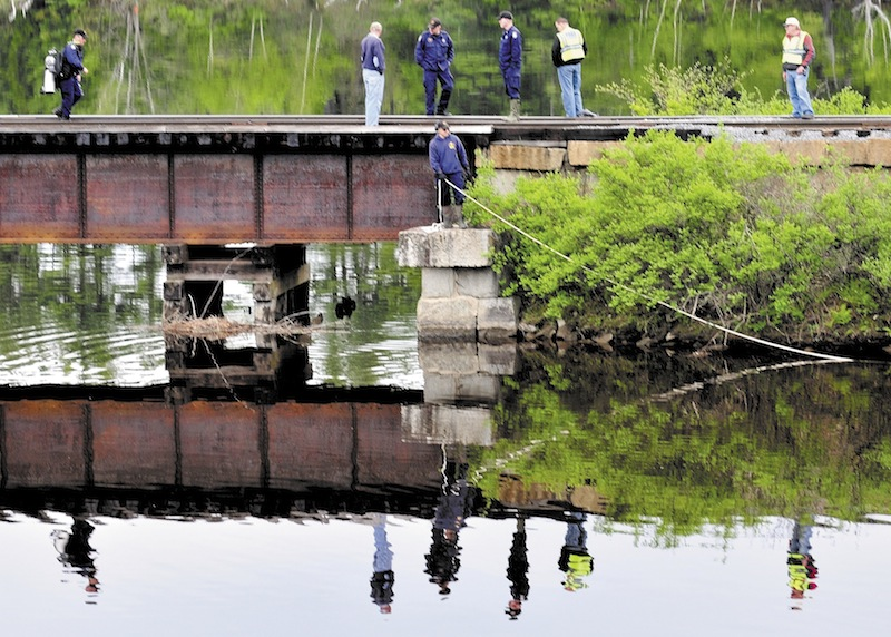 Maine State Police divers search Martin Stream near the Kennebec River off U.S. Route 201 in Hinckley on Sunday for the body of a woman driver after her vehicle left the road late Saturday evening.