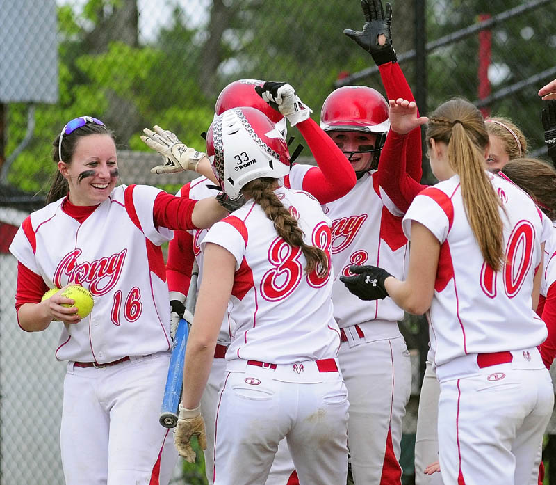 Staff photo by Joe Phelan Cony teammates congratulate Nicole Rugan as she crosses the plate after hitting a very long two run homer in third inning of a game on Wednesday evening at Cony Family Field in Augusta.