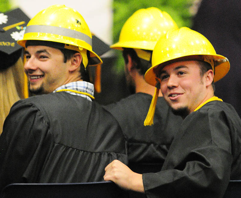 Chris Murphy, left, and Nathan Nixon, along with most of their Electrical Lineworker Technology fellow graduates, wore bright yellow hard hats instead of mortarboards for KVCC's graduation.