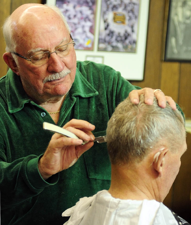 Francis Lorette shaves around Warrren Hayward's ears on Tuesday afternoon at Lorette's Barber Shop in Winthrop. Hayward didn't know that Lorrete had closed last Saturday. Since he'd stopped Lorrette gave a haircut and joked that Warren would be in trouble with is wife if he'd said he went out for a haircut but didn't one. Lorette closed his 49-year-old business last Saturday, but did two last haircuts on Tuesday afternoon before packing up his clippers.