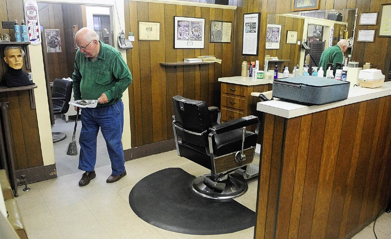 Francis Lorette sweeps up hair from the floor on Tuesday afternoon at Lorette's Barber Shop in Winthrop. Lorette closed his 49-year-old business on Saturday afternoon, but did two last haircuts on Tuesday afternoon before packing up his clippers.