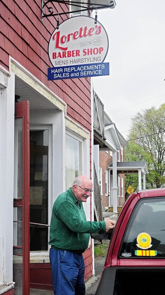 Francis Lorette shakes hands with a customer who stopped by to chat when he saw the barber outside Lorette's Barber Shop on Tuesday afternoon in Winthrop. Lorette closed his 49-year-old business on Saturday afternoon, but did two last haircuts on Tuesday afternoon before packing up his clippers.