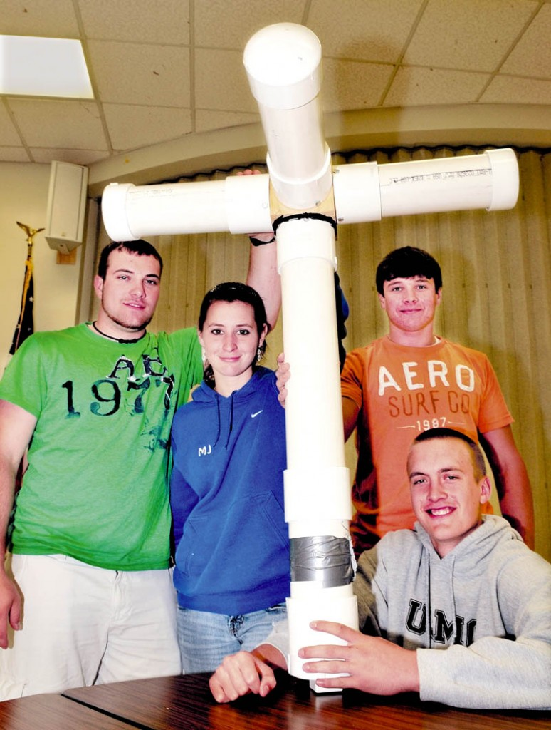 """THE BEAST: Madison Area Memorial High School students hold their project called the """"Floating Beast,"""" a scale model offshore, floating, wind-turbine platform. From left are Travis Emerson, Jess Thebarge, Matt Soucy and Stephen Cusson, seated."""