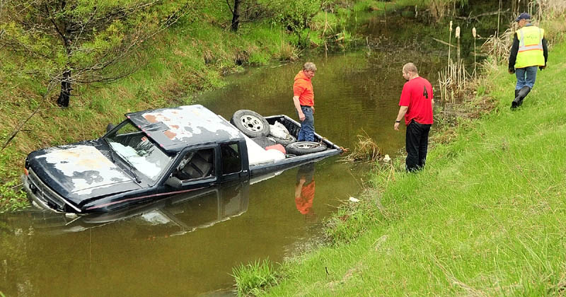 SUBMERGED: Driver Shane Sours, 37, of Starks, stands on shore talking to wrecker operators who are pulling his 1992 Dodge Dakota out of a drainage ditch on Wednesday in West Gardiner. One person suffered minor injuries when the pickup truck skidded off Interstate 95 and ended up partially submerged. Maine State Police Trooper Niles Krech said the crash occurred around 1:45 p.m., when Sours blacked out briefly during a coughing attack while driving on the southbound off ramp at exit 103. The truck hit a guardrail and caromed down an embankment into the ditch. Krech said water flooded the truck to the seats inside the cab.