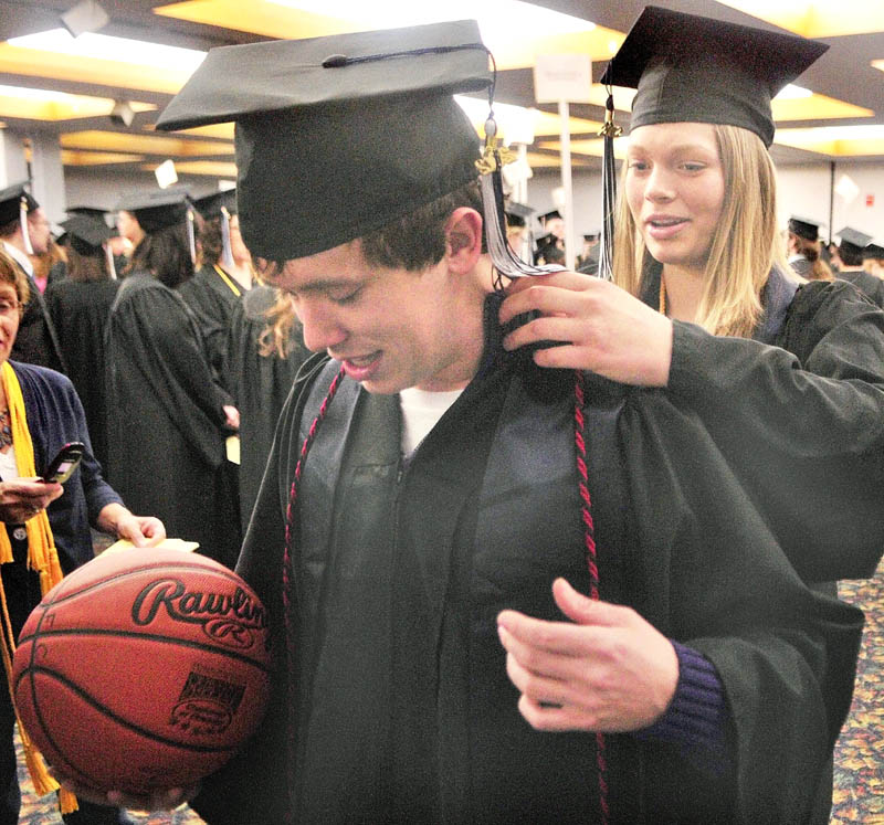 Marty Campbell, of Whitefield, left, gets some help straightening out his sash and cord from fellow graduate Katie Poirier, of Harmony before the University of Maine at Augusta graduation exercises on Saturday morning in the Augusta Civic Center. They had both played for the University's basketball teams.