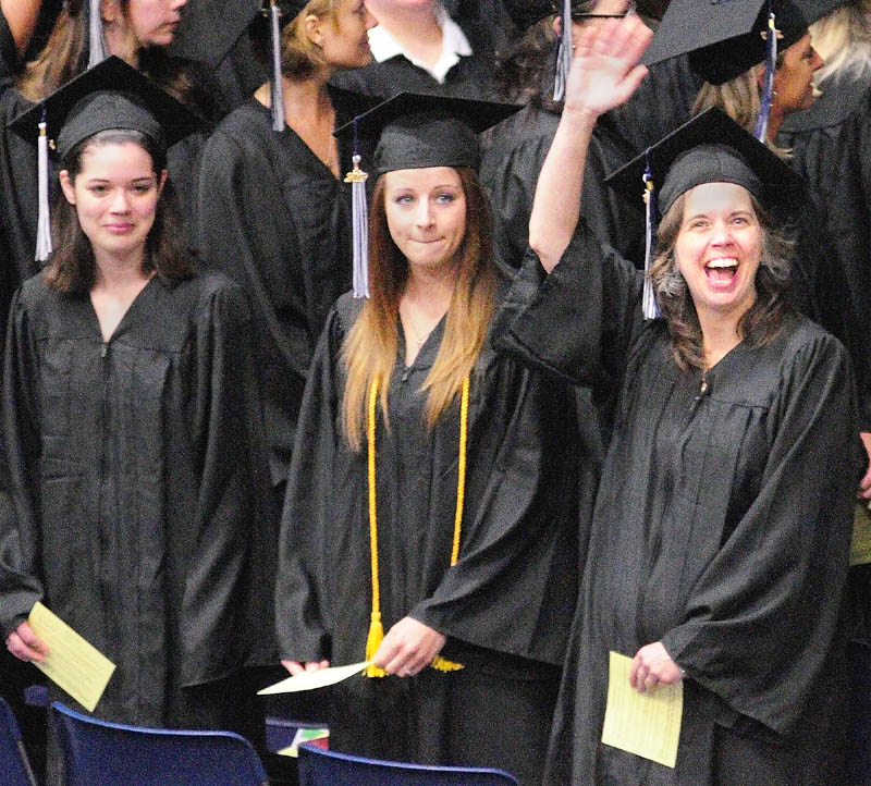 Shelley Vermillion, of Gardiner, right, waves to her family after marching into the Augusta Civic Center for the University of Maine at Augusta graduation exercises on Saturday morning.