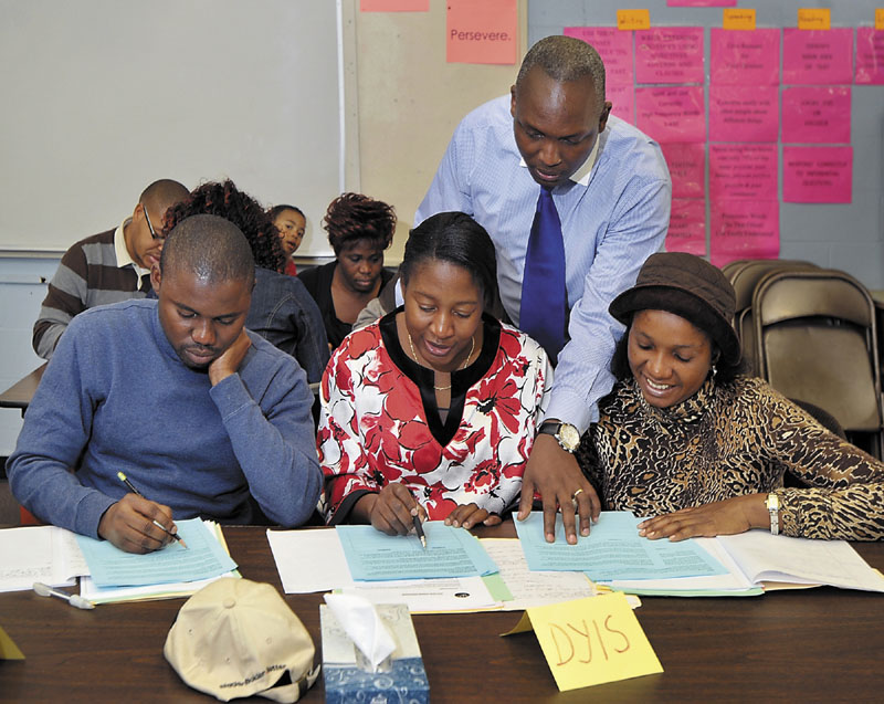 Assistant teacher, Clement Yombe, helps French speaking students with their class work during a class on responsible finance management at the Portland Adult Education Center taught by Claude Rwaganje. Students are from left: Rufus Mfinji, Dyis Mukadi and Liliane Ngituka.