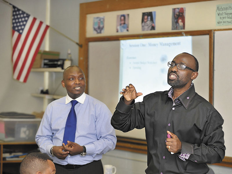 """Claude Rwaganje, right, teaches a class on responsible finance management at the Portland Adult Education Center. He is helped by assistant teacher, Clement Yombe, who also translated for the French speaking students who attend with other immigrants, low-income and """"unbanked"""" residents."""
