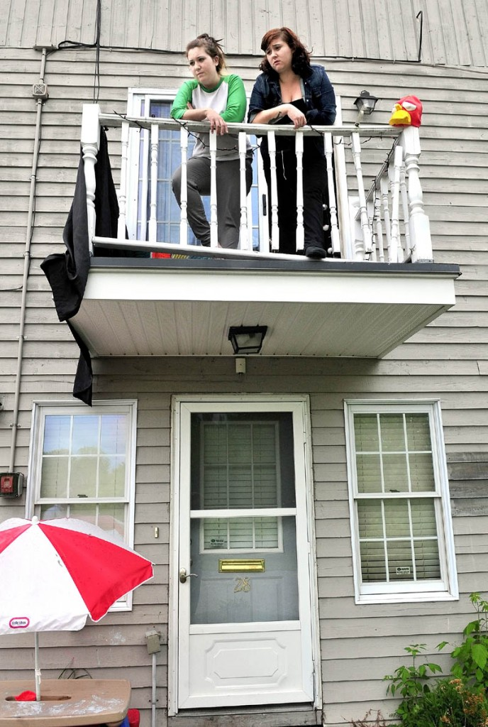 QUIET NEIGHBORHOOD: Abby Witham, left, and her sister Katie speak from a balcony outside their apartment at Averill Condominiums in Waterville on Tuesday. They recounted watching armed undercover police officers storm out of the nearby woods to confront a male condominium resident who arrived Tuesday morning and was taken into custody.