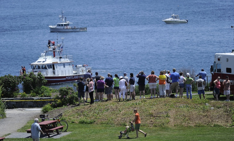 A crowd gathers at Fort Williams Park in Cape Elizabeth at the scene of a plane crash in Casco Bay on Sunday