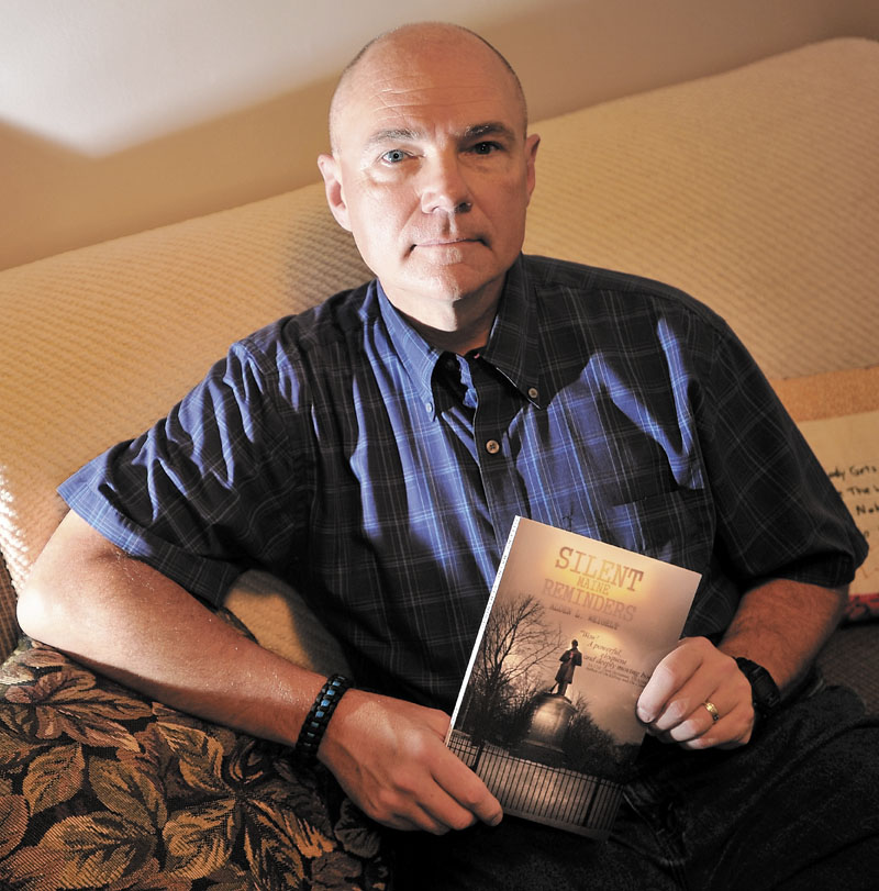 """Waterville police officer Alden Weigelt holds a copy of his book """"Silent Maine Reminders"""" at his home in Winslow on Thursday."""