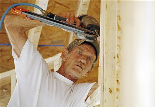John Knight uses an air hammer as he frames a new house on a lot in Pearl, Miss., recently. Confidence among U.S. builders ticked up in June to a five-year high, an indication that the housing market is slowly improving.