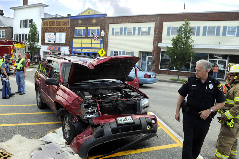 Police and firefighters inspect a sport utility vehicle that crashed Thursday in downtown Winthrop while being pursued by Maine State Police. State trooper Dane Wing arrested Glen Harrington after police said he crashed into two trucks and fled on foot.