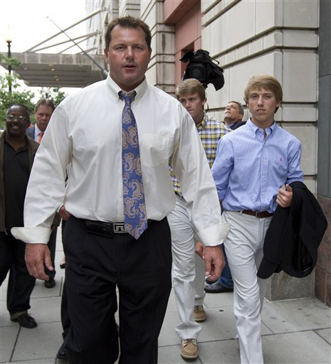 Former Major League Baseball pitcher Roger Clemens, left, gestures as he leaves Federal Court in Washington with sons, Kacy, center back, and Kody, right, in this June 12, 2012, photo.
