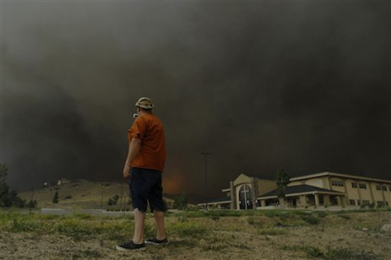 A man stops quickly to get some video before running away from approaching flames of the Waldo Canyon Fire as it raced down into western portions of Colorado Springs, Colo. on Tuesday, June 26, 2012 leaving a trail of destruction and burning homes and buildings in its path. Heavily populated areas in the fire's path have been affected. (AP Photo/Bryan Oller) Bryan Oller;Waldo Canyon Fire;Colorado Springs Fire;forest fire