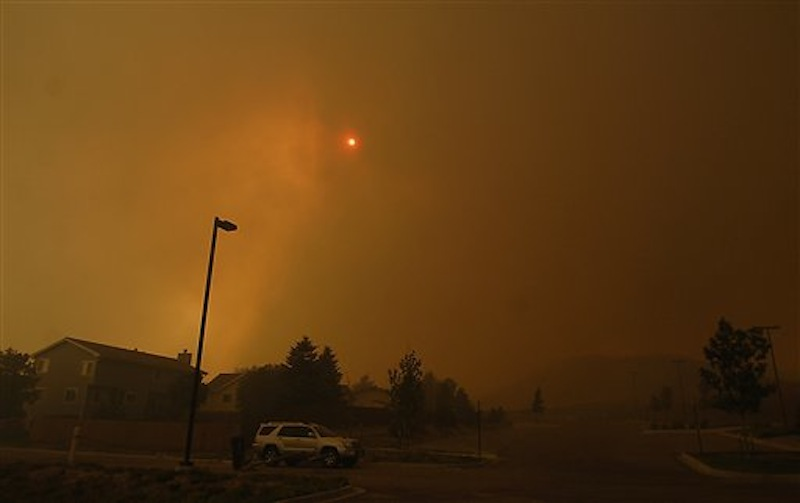 The skies are orange as flames from the Waldo Canyon Fire race through a neighborhood in west Colorado Springs, Colo. on Tuesday, June 26, 2012 leaving a trail of destruction, burning homes and buildings in its path. Heavily populated areas in the fire's path have been affected. (AP Photo/Bryan Oller) Bryan Oller;Waldo Canyon Fire;Colorado Springs Fire;forest fire