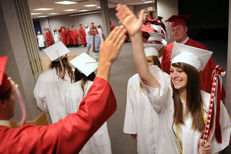 Cony High School class of 2012 marshall Natalie Arbour exchanges a high-five with classmate Dylan Cheever during their graduation ceremony Sunday in Augusta.