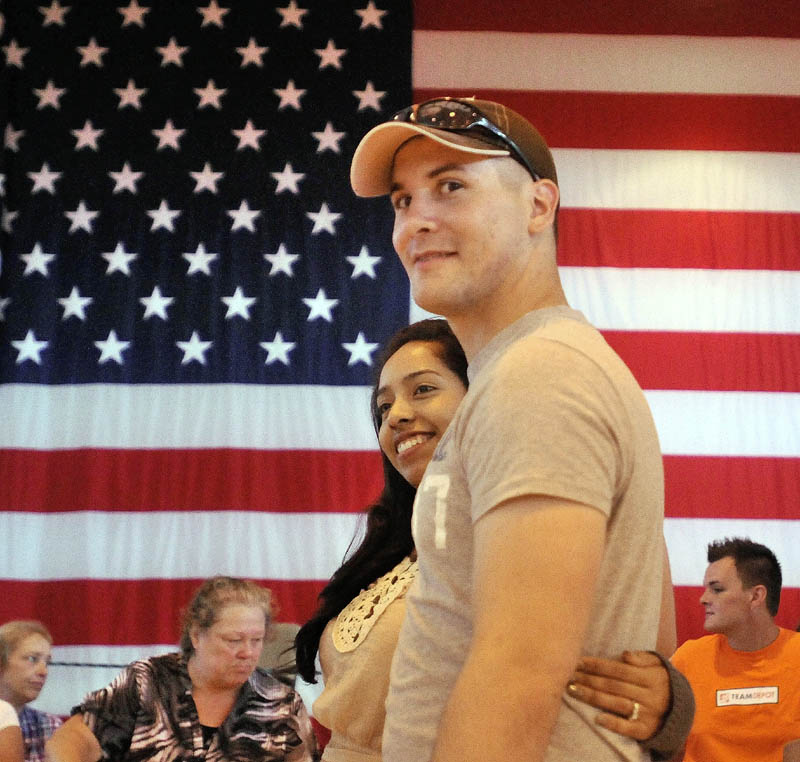 Army Spc. Jason Pepin, center, and his wife Estela, wait in line for hot food during a family barbecue Sunday at the Waterville Armory. Jason Pepin is one of 125 soldiers with the 488th Military Police Company of the Maine National Guard preparing to deploy to Afghanistan next week.
