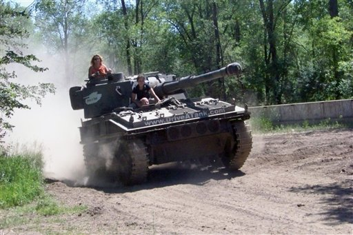 Marvin Bourne of Richmond, Va., drives a tank in Kasota, Minn., while his wife Karen Bourne looks out from the turret and Drive-A-Tank employee Kessa Baedke sits behind him.