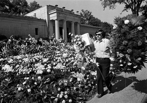 """In this Aug. 18, 1977 file photo, a florist adds more floral arrangements to the overflowing collection of flowers that cover the ground at the mausoleum where singer Elvis Presley will be entombed during funeral services today in Memphis, Tenn. Celebrity auctioneer Darren Julien says the crypt inside the granite and marble mausoleum where Presley was originally entombed at the Forest Hill Cemetery in Memphis, Tenn., will be part of his """"Music Icons"""" auction on June 23 and 24, 2012, in Beverly Hills, Calif. (AP Photo, File)"""