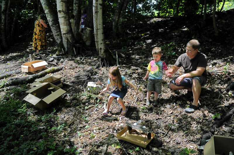 Katelin Sieberg, 5, sets out a fairy house with her brother, Tyler, 3, and father, Rick, Thursday in Gardiner.