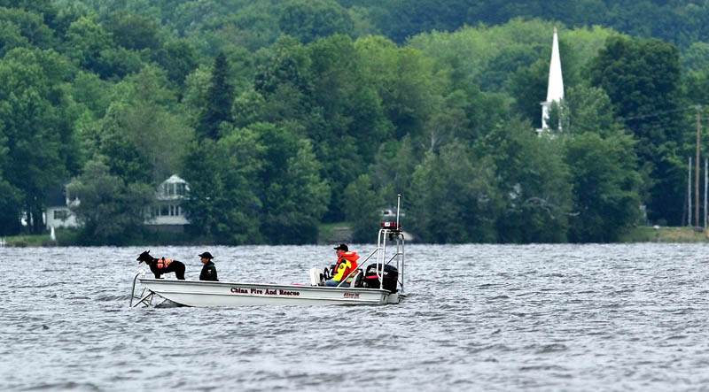 Searchers with the Maine Warden's Service search an area of China Lake for missing swimmer, Tye Feihel, 43, on Tuesday. Feihel was reported missing when he didn't return from his usual afternoon swim.