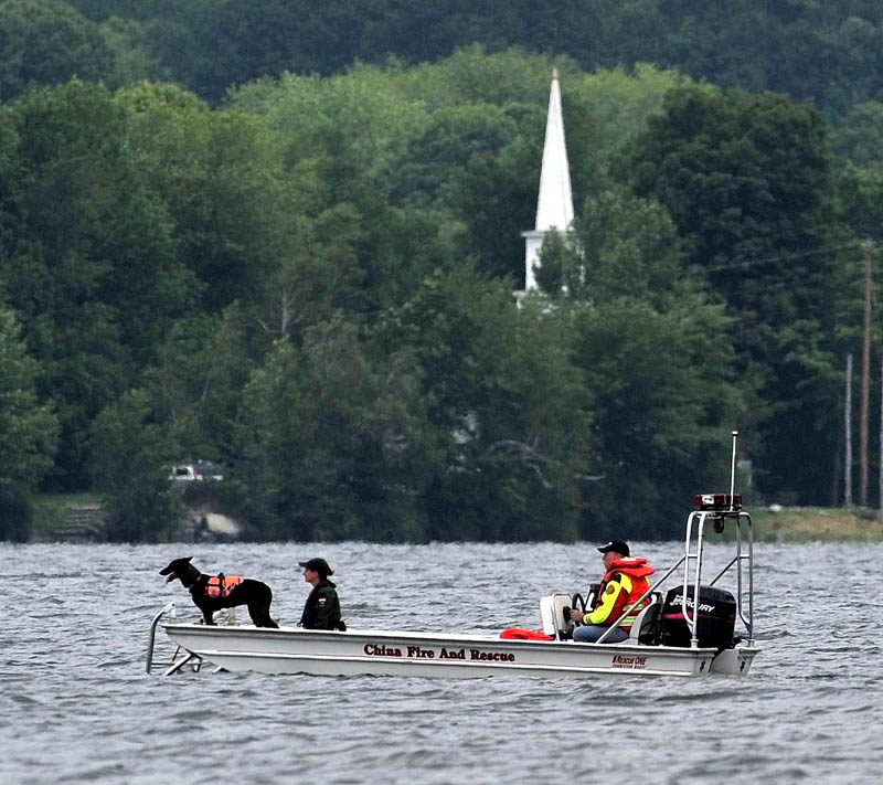 CHINA LAKE: Searchers with the Maine Warden Service scan an area of China Lake for missing swimmer Tye Feihel, 43, on Tuesday. Feihel was reported missing when he didn't return from his usual afternoon swim.