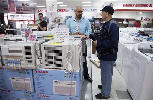 Salesman Carlos Burgos, center, helps customer Raven Campbell select an air conditioner at P.C. Richard & Son, an electronics and appliance store on Tuesday in the Brooklyn borough of New York.