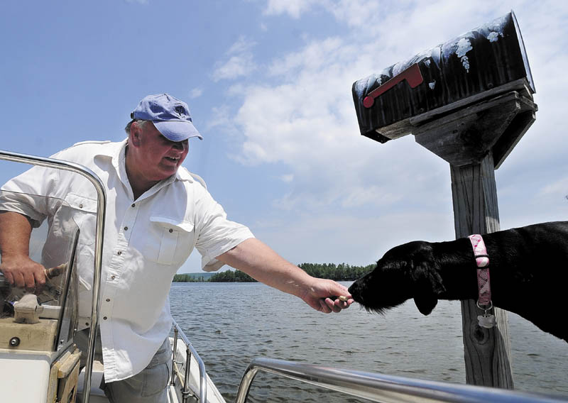 Norm Shaw gives a dog biscuit to a dog on mail route on Thursday in Belgrade. He has been delivering the mail from his boat on Great Pond in Belgrade and Rome for nine years.