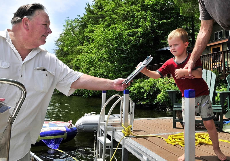 Norm Shaw, left, hands off the mail to a youngster while making deliveries from his boat on Thursday in Belgrade.