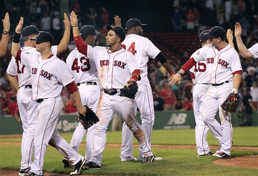 Boston Red Sox players, including shortstop Mike Aviles, center, celebrate their 15-5 victory over the Miami Marlins in an interleague baseball game at Fenway Park in Boston on Wednesday, June 20, 2012. (AP Photo/Elise Amendola)
