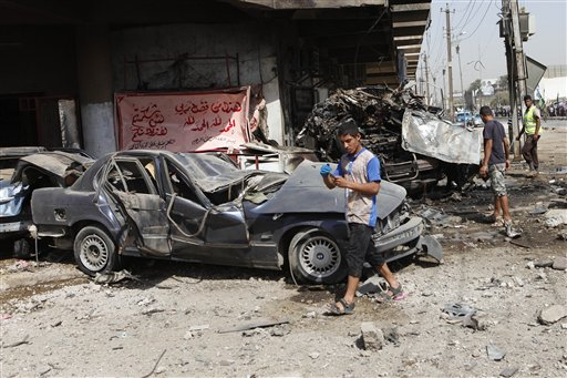 People inspect the scene of a car bomb attack in the Karrada neighborhood of Baghdad today.