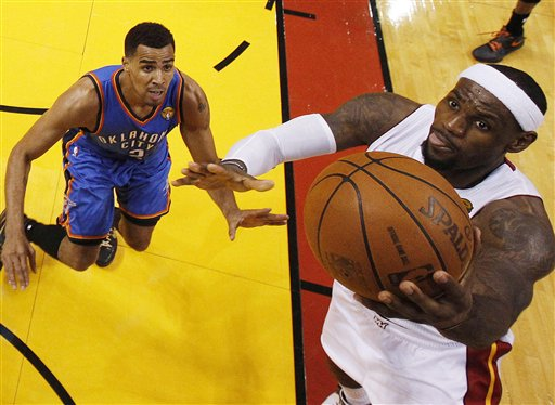 Miami Heat small forward LeBron James (6) shoots as Oklahoma City Thunder shooting guard Thabo Sefolosha (2) of Switzerland defends during the second half at Game 4 of the NBA finals basketball series, Tuesday, June 19, 2012, in Miami. The Heat won 104-98. (AP Photo/Mike Segar, Pool)