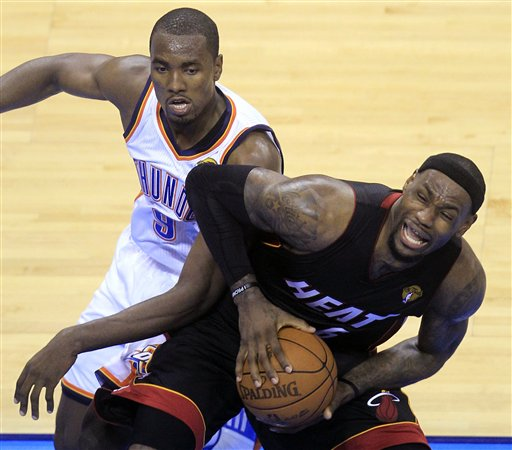 Miami Heat small forward LeBron James is defended by Oklahoma City Thunder power forward Serge Ibaka (9) from Republic of Congo during the first half at Game 2 of the NBA finals basketball series, Thursday, June 14, 2012, in Oklahoma City.