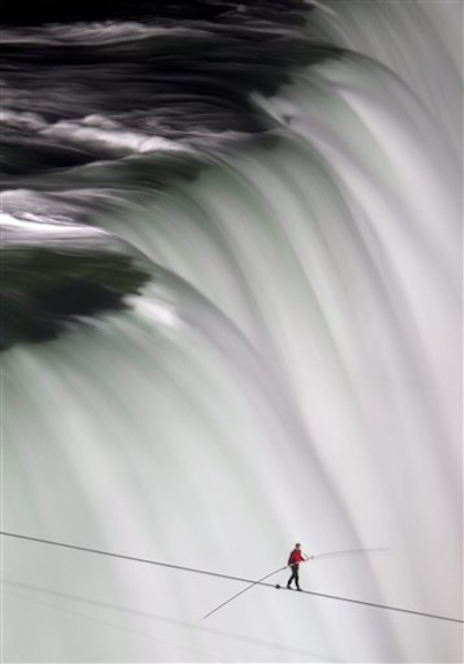 Nik Wallenda walks over Niagara Falls on a tightrope in Niagara Falls, Ontario, on Friday, June 15, 2012. Wallenda has finished his attempt to become the first person to walk on a tightrope 1,800 feet across the mist-fogged brink of roaring Niagara Falls. The seventh-generation member of the famed Flying Wallendas had long dreamed of pulling off the stunt, never before attempted. (AP Photo/The Canadian Press, Frank Gunn) general;art;artistic;arts;Canada;Canadian;Ent;entertain;entertainer;entertainers;entertaining;entertainment;performance;performing;expression;image;photograph;photographed;picture;portraits;pose;poses;posing;profile;portrait;Falls;Tight;Tight rope;Walk;Danger;Water;Waterfalls;United States;USA;Wire;Conditions;Wet;River;Hight;Fall;Slip;Mist;Lights;Distance;Feet;Meters;Audience;High;Balance;Pole;Beam;Victory;Accomplish;balance beam;acrobat;acrobatics;apparaus;athlete;athletes;athletic;athletics;competative;compete;competing;competition;competitions;event;exercise;gym;parallel;rhythm;routine;skill;skills;sport;sporting;sports;gymnastics
