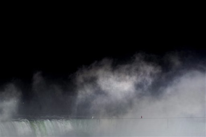 Nik Wallenda walks a tightrope over Niagara Falls as seen from Niagara Falls, Ontario, on Friday, June 15, 2012. Wallenda has finished his attempt to become the first person to walk on a tightrope 1,800 feet across the mist-fogged brink of roaring Niagara Falls. The seventh-generation member of the famed Flying Wallendas had long dreamed of pulling off the stunt, never before attempted. (AP Photo/The Canadian Press, Nathan Denette) general;art;artistic;arts;Canada;Canadian;Ent;entertain;entertainer;entertainers;entertaining;entertainment;performance;performing;expression;image;photograph;photographed;picture;portraits;pose;poses;posing;profile;portrait;Falls;Tight;Tight rope;Walk;Danger;Water;Waterfalls;United States;USA;Wire;Conditions;Wet;River;Hight;Fall;Slip;Mist;Lights;Distance;Feet;Meters;Audience;High;Balance;Pole;Beam;Victory;Accomplish;balance beam;acrobat;acrobatics;apparaus;athlete;athletes;athletic;athletics;competative;compete;competing;competition;competitions;event;exercise;gym;parallel;rhythm;routine;skill;skills;sport;sporting;sports;gymnastics